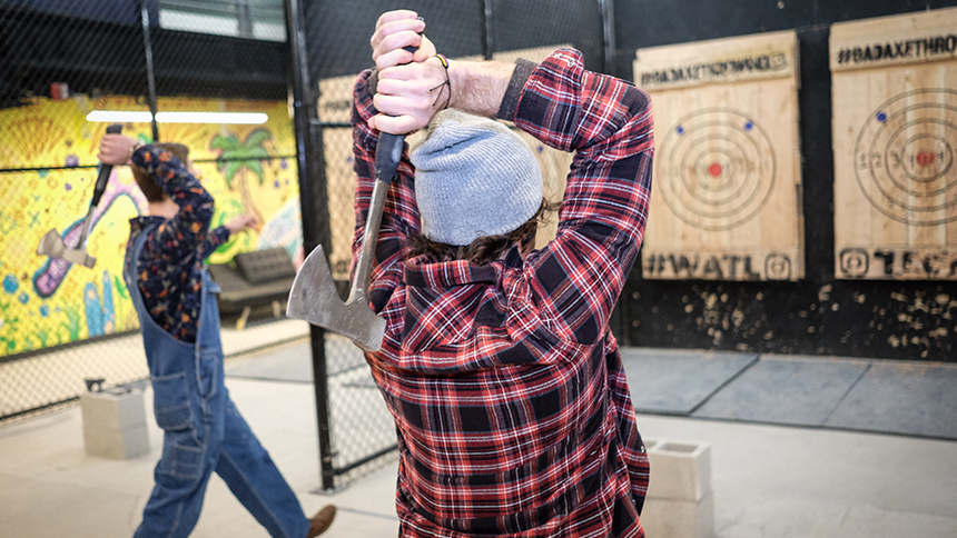 Two men wearing flannel shirts engage in simultaneous tow handed ax throws into a wooden target at Bad Axe Throwing in Chicago