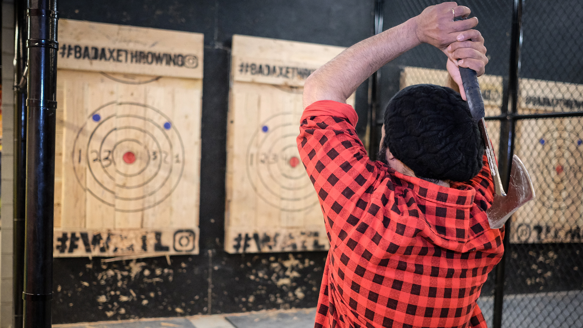 A man in red and black checkered flannel uses two hands to throw an axe at Bad Axe Throwing in Chicago
