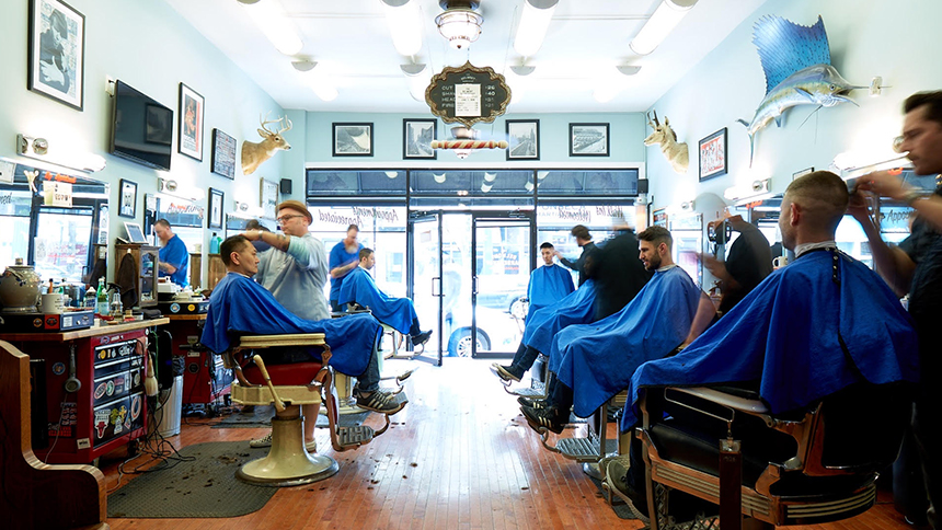 Barbers from Belmont Barbershop in Chicago cut, buzz and trim the hair of male patrons