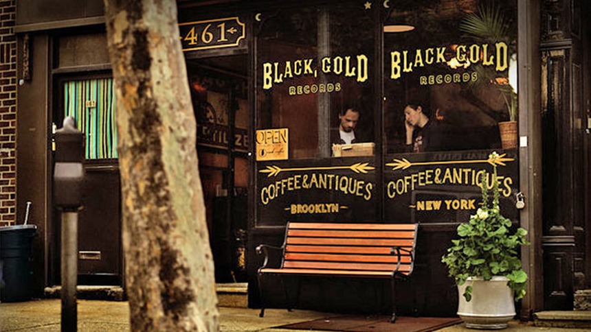 A man and woman sit in the front window of Black Gold Record and Coffee Shop in New York City