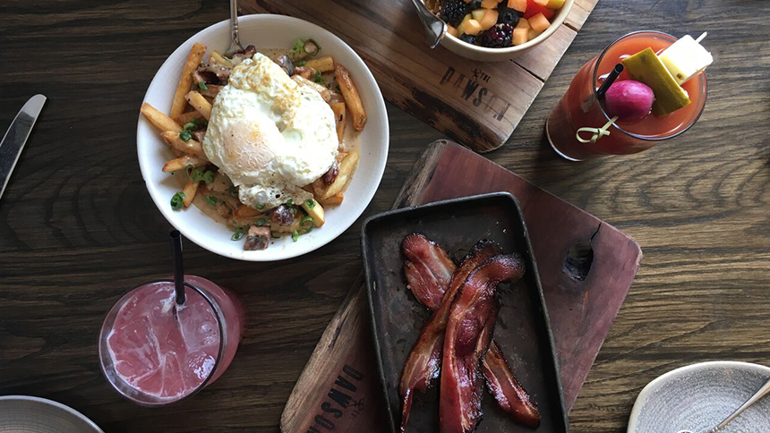 A full spread of brunch is displayed from The Dawson in Chicago, including bloody mary, grapefruit juice, a fried egg atop fries and a rasher of bacon
