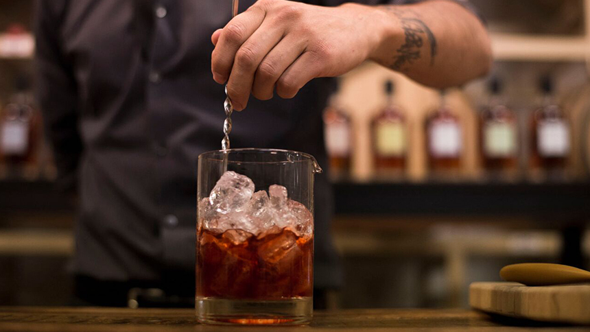 A man's tattooed arm stirs a whiskey cocktail at at bar top during a cocktail class in Koval Distillery in Chicago