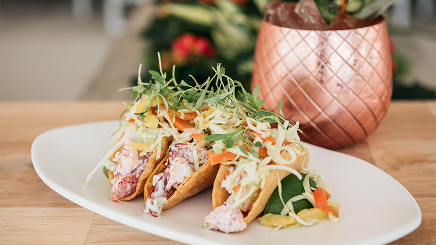 Three lobster tacos from Shore Club in Chicago rest perfectly garnished on a white plate with a copper mug of mixed drink in the background