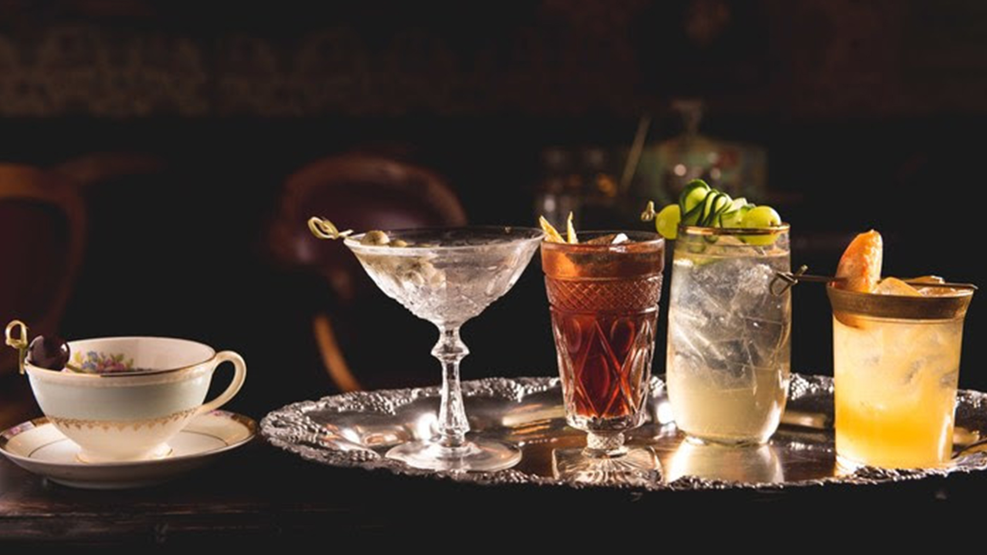 A silver platter holds three distinct types of upscale mixed drinks alongside a coffee cup