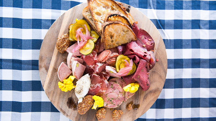 A platter consisting of various types of meats and breads sits on a blue and white checkered table cloth