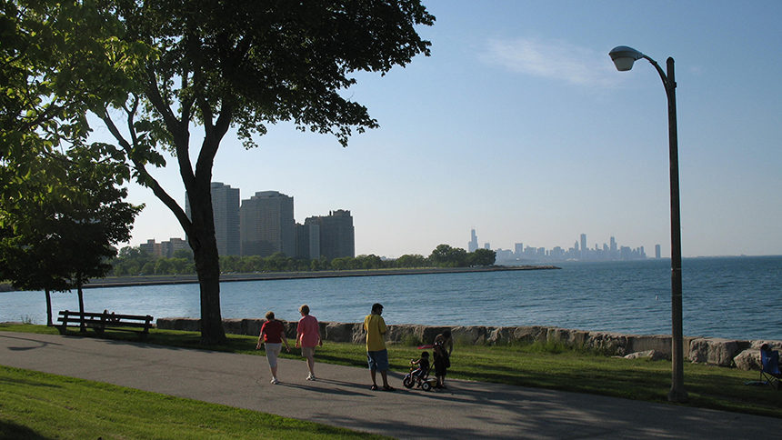 People walk along the sidewalk hemming Promontory Point in Chicago