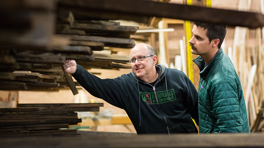 An employee from Rebuilding Exchange in Chicago shows a customer pieces of reclaimed wood