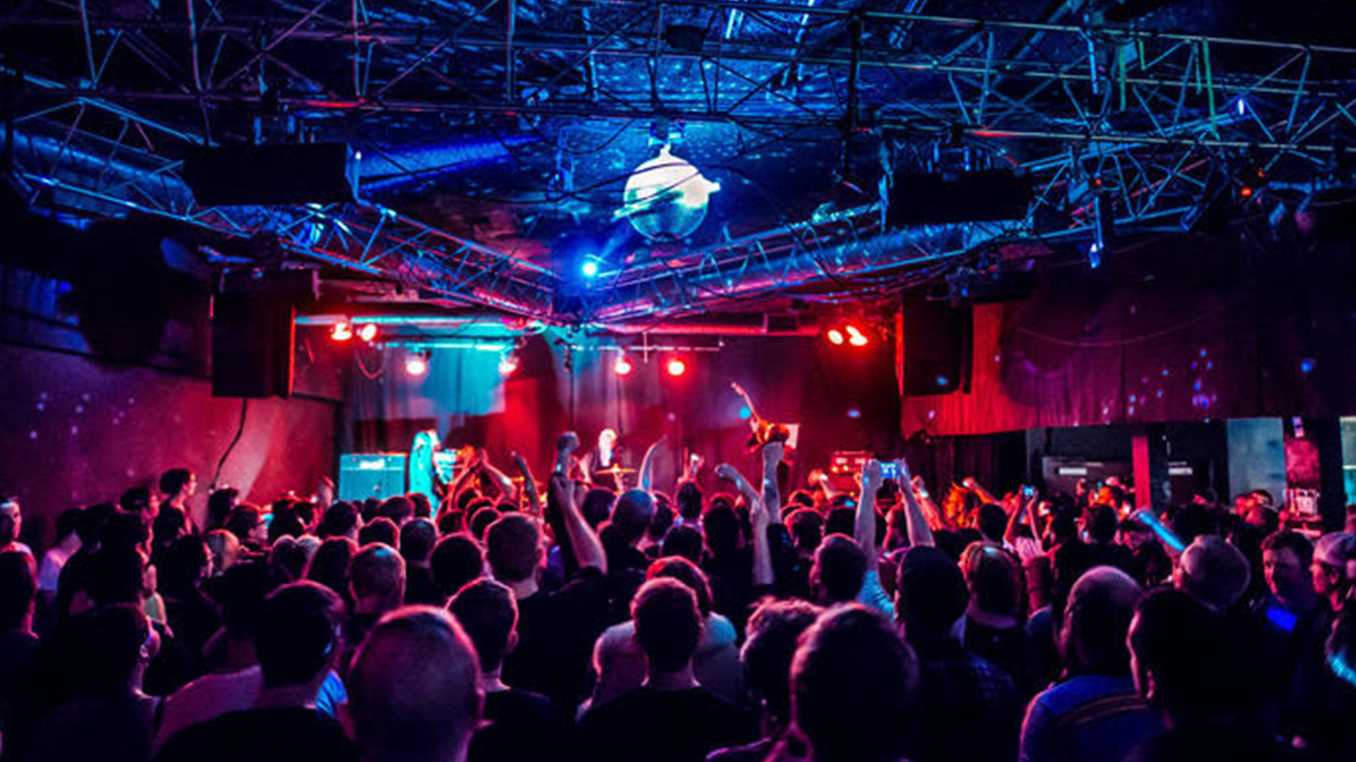 An image of a crowd at Satellite bathed in a red and blue light