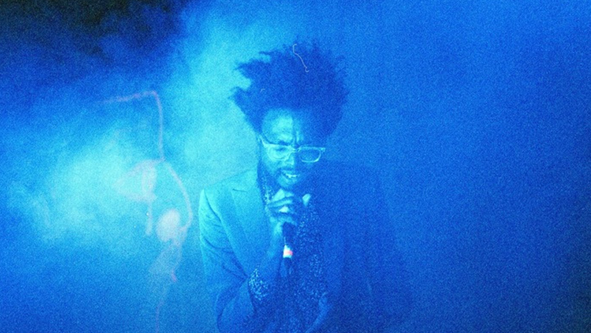 An image of Tolliver singing in blue light