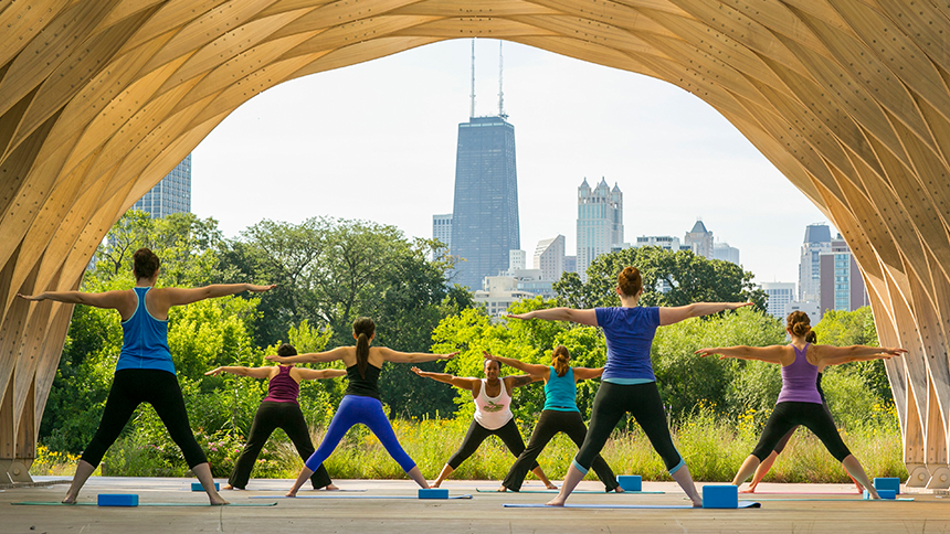 An image of people exercising at Lincoln Park to a Chicago cityscape background
