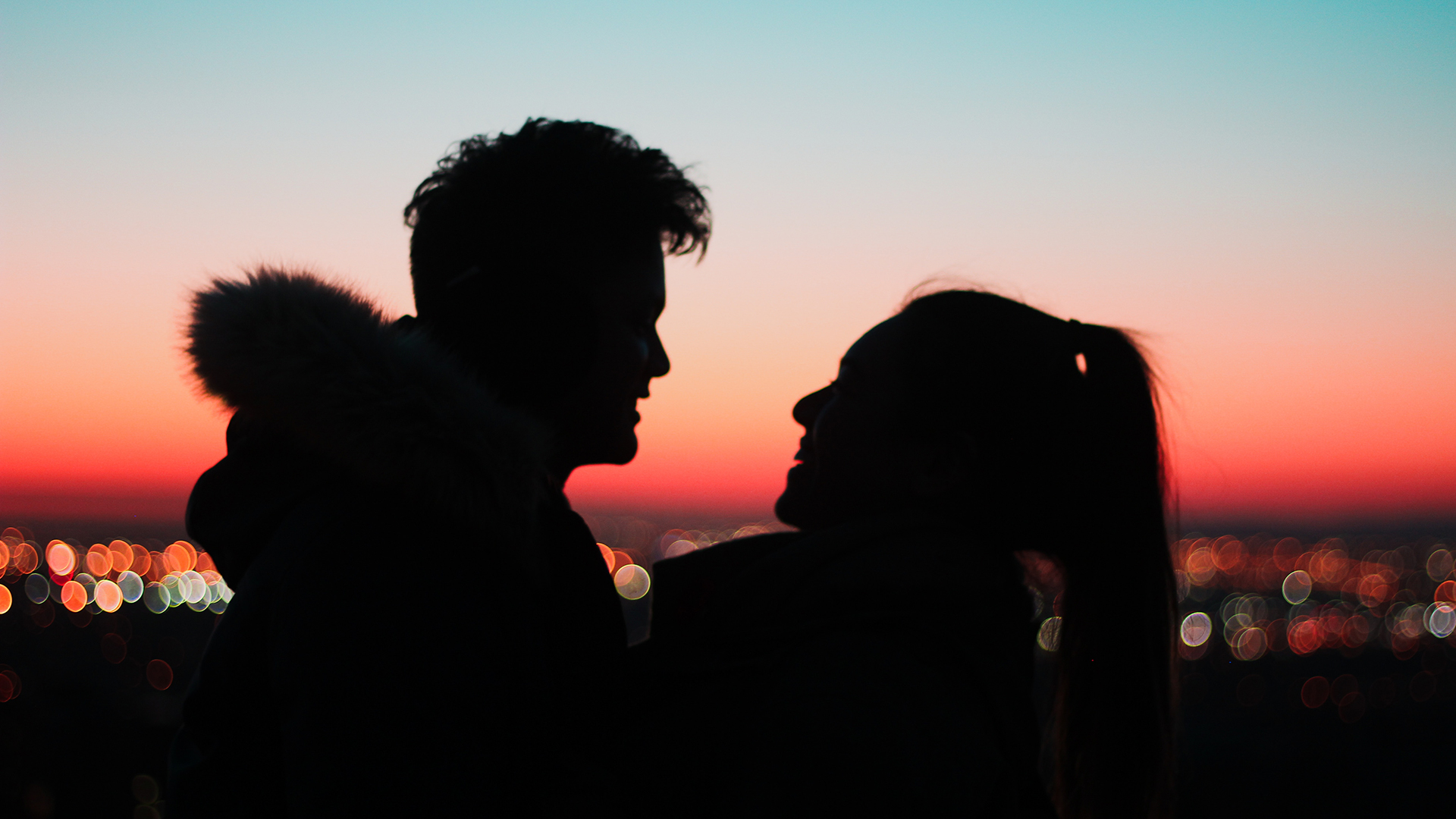 Two people embrace in the foreground of a cityscape