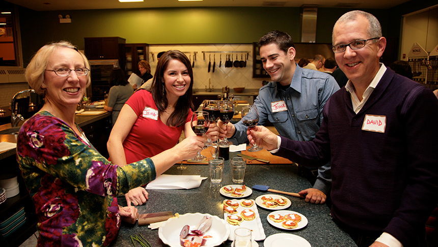 Two couples toast at the Chopping Block in Chicago, Illinois after cooking their own meal