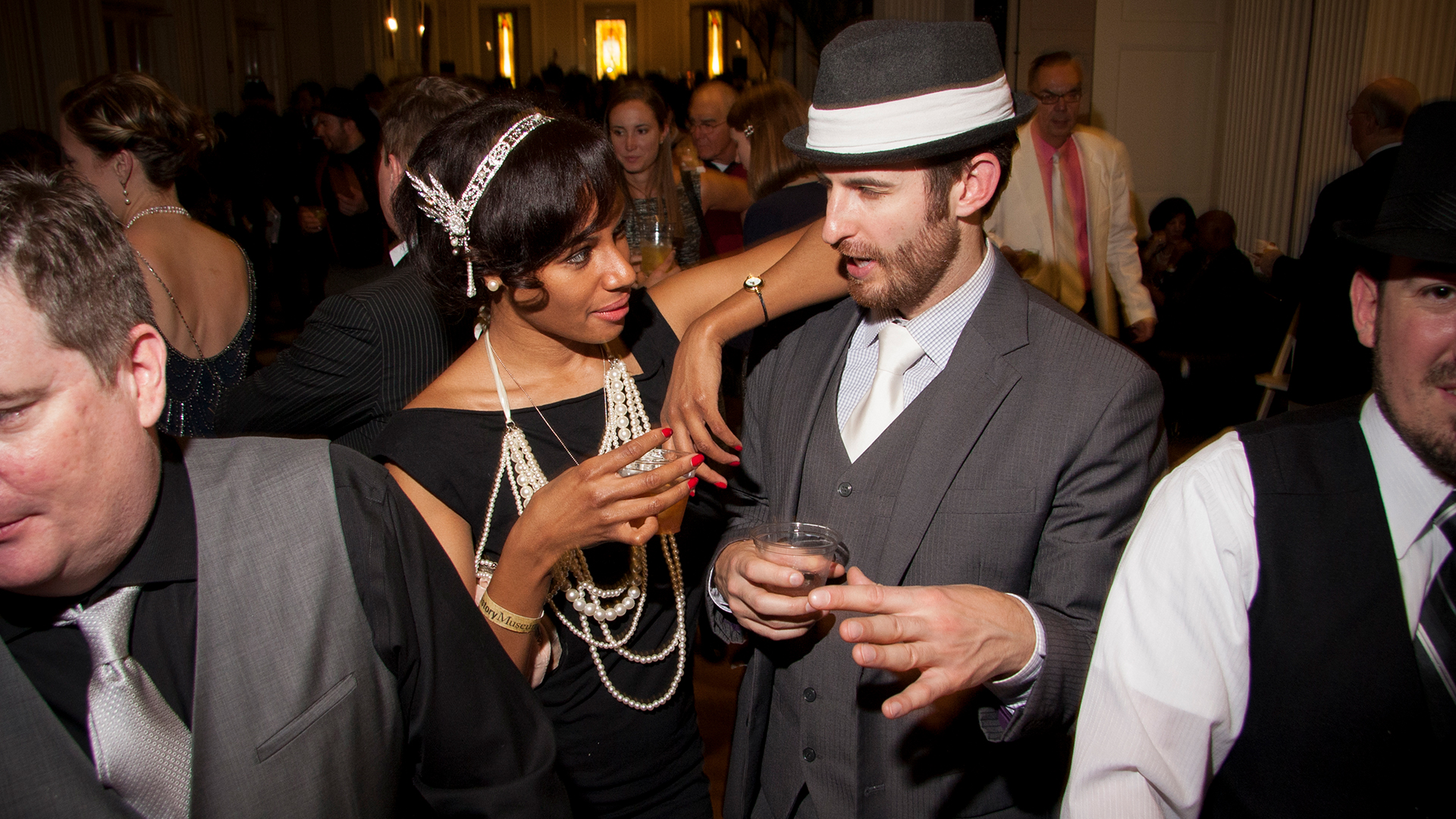 A couple dressed in Prohibition era clothing chatting and having drinks