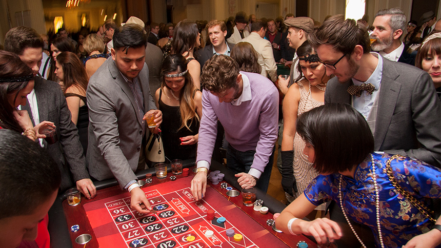 A group of people dressed in Prohibition era clothing playing craps