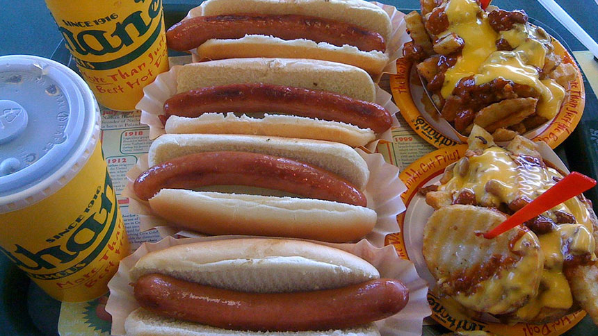 A tray from Nathan's Famous in Coney Island containing hot dogs and chili cheese fries